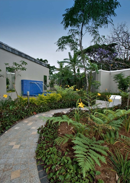 "Jardine Landscape Designs (072 952 3904). The majority of this garden was landscaped around its existing shrubbery. However the experts from Jardine Landscape Designs replaced the tennis court with a ""secret garden"" using all new material. The landscapers also designed and installed a fully automated irrigation system, 140m² of granite pathways and a water feature. Adding the finishing touches to this outdoor haven are various pots and an impressive bench."