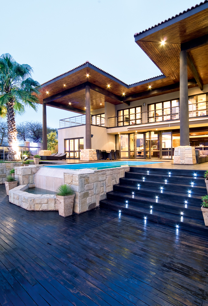 modern mansion with pool and palm trees